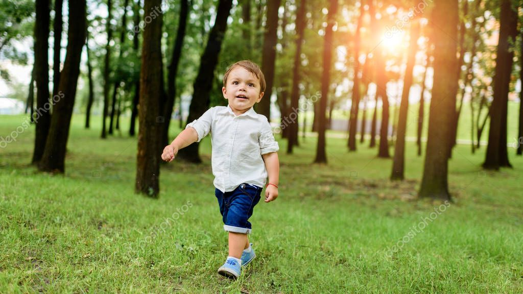 cute little kid in white shirt and denim shorts running by park