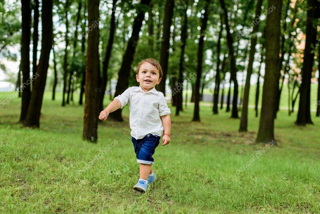 smiling little kid in white shirt and denim shorts running by park