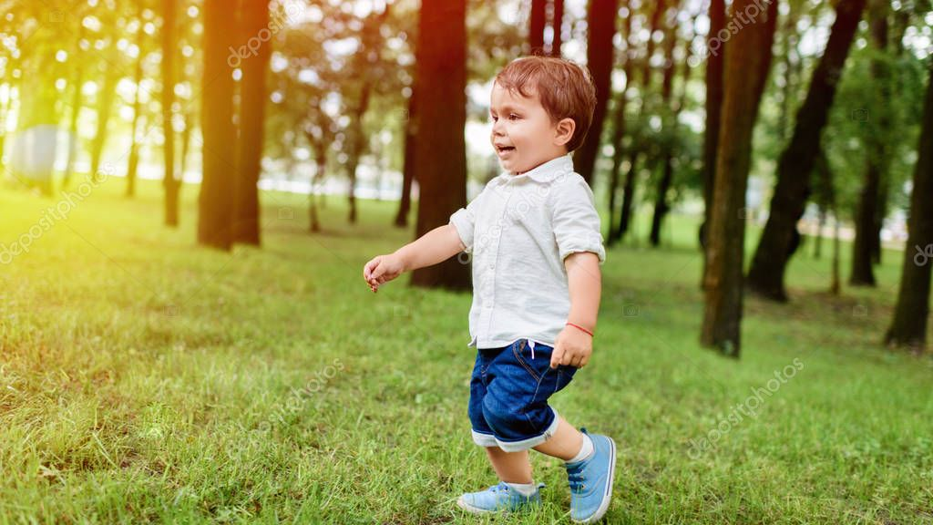 happy little kid in white shirt and denim shorts running by park