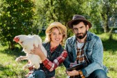 happy woman holding chicken while her boyfriend making notes in clipboard at farm