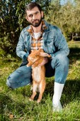 happy male farmer holding brown rabbit  and looking at camera outdoors