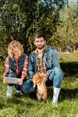 Fotografie smiling male farmer holding brown rabbit while his girlfriend using digital tablet on grass at ranch