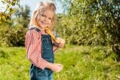 kis gyerek imádnivaló sárga bébi csirke gazdaság és látszó-on fényképezőgép szabadban
