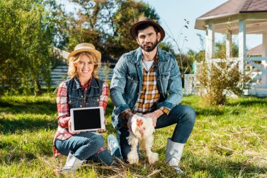 woman showing digital tablet with blank screen while her boyfriend holding chicken at farm