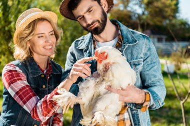 smiling couple of farmers in straw hats with chicken at farm