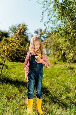happy cute child holding adorable yellow baby chick outdoors