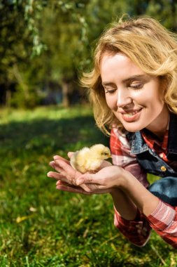 attractive woman holding adorable yellow baby chick outdoors