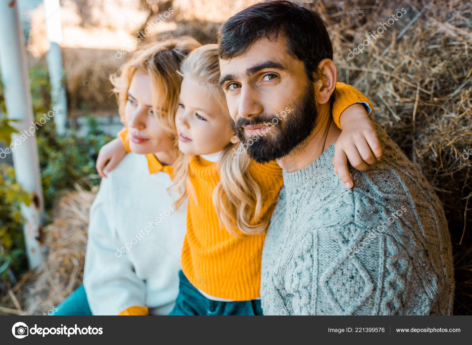 Adult male farmer looking at camera while his family sitting behind at farm