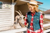 Photo beautiful smiling woman touching goat near wooden fence at farm