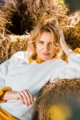 portrét krásné ženy při pohledu na fotoaparát a položil na hromádky sena na farmě