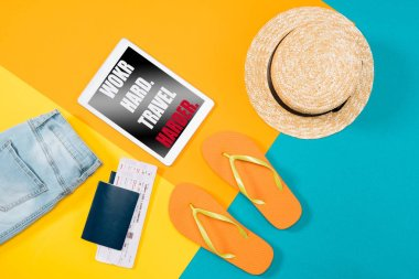 Top view of orange flip flops, passports, ticket, digital tablet and clothes on colored background.  Essential vacation items. lettering -