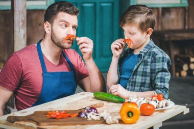 little boy with father doing moustaches with slices of pepper while cooking at table