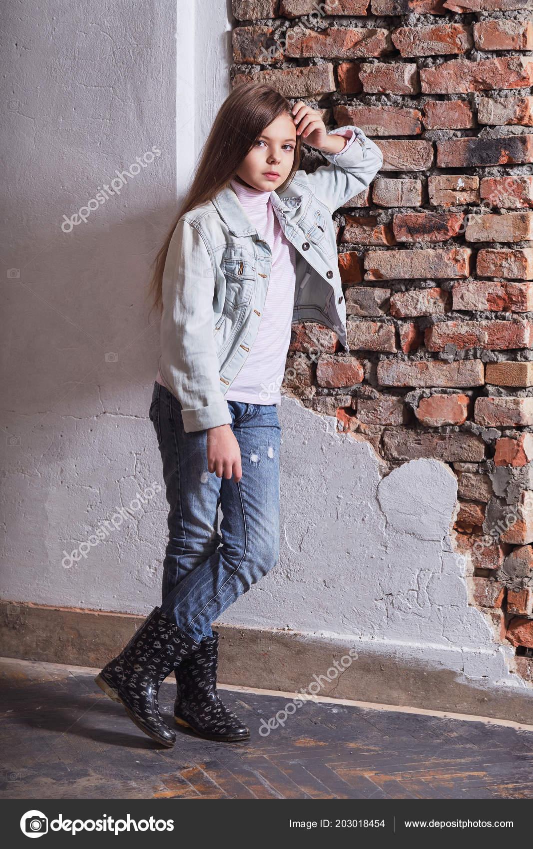 fef68619ea Parede de tijolo de inclinada de pé de menina de moda. Garoto modelo  elegante. Criança caucasiana em casuais roupas elegantes