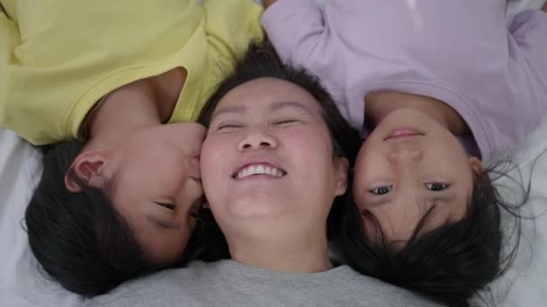 Asian mother and her daughters cuddling in bed, Funny mom and lovely childs are having fun.