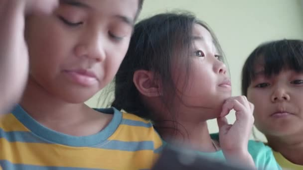 Asian children's group using smart phone or tablet at home.