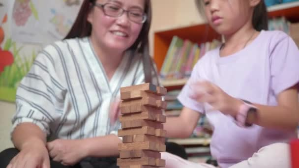 Happy asian family, Young mother and her daughter try to build wooden block tower.