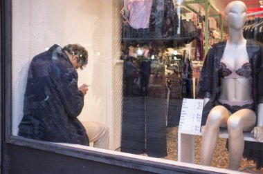 VENEZIA, ITALY - OCTOBER 7, 2018: waiting for his wife to finish shopping, man sit spend time with his phone