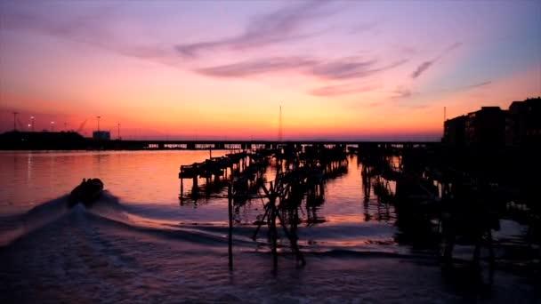 Sonnenuntergang über der Lagune von Chioggia (Italien) mit einem vorbeifahrenden Boot und Muschelzucht