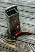 Fotografie Rote Chilischote mit Metall Reibe auf Holztisch