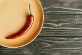 Červené pálivé papriky podávané na talíř na dřevěný stůl