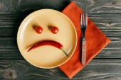 Photo Sad smiley made of pepper and tomatoes on plate with fork on orange napkin