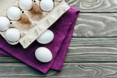 Photo Carton box with white eggs on purple napkin