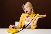 Photo beautiful stylish blonde woman in yellow clothes using rotary phone while sitting on brown