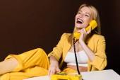fröhliches blondes Mädchen, das mit gelbem Vintage-Telefon spricht und über braun lacht