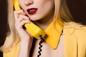 Fotografia ritagliata colpo di giovane donna sensuale che comunica dal telefono vintage giallo