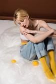Fotografia vista di alto angolo di pensosa ragazza bionda elegante seduto e guardando la pagina di limoni su colore marrone