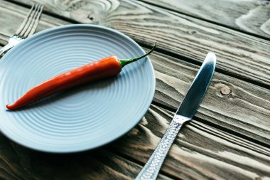 Red chili pepper on plate with knife and fork on wooden table