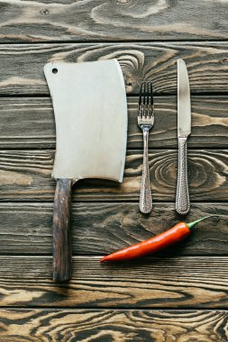 Silverware and cleaver with red chili pepper on wooden table