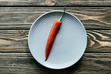Red hot pepper served on plate on wooden table