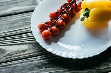 Plate with cherry tomatoes and bell pepper on wooden table