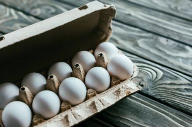Carton box with white eggs on wooden table