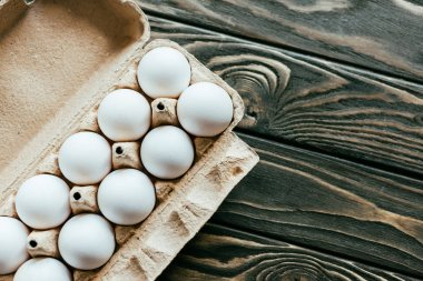Carton container with chicken eggs on wooden table