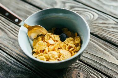 Breakfast with corn flakes and blueberries on wooden table