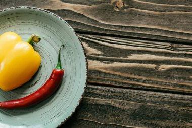 Plate with chili and bell peppers on wooden table