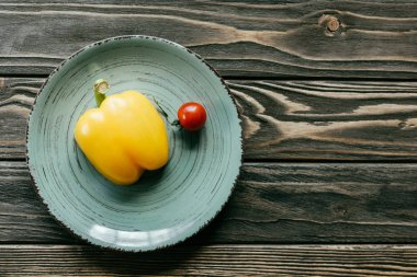Bell pepper and cherry tomato on plate on wooden table