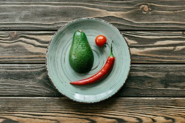 Chili pepper with avocado and cherry tomato in plate on wooden table