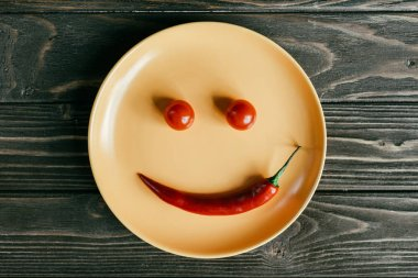Plate with smile made of pepper and tomatoes on wooden table