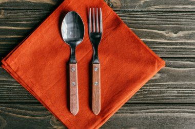 Silverware set with orange napkin on wooden table
