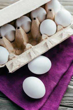Chicken eggs in box on purple napkin
