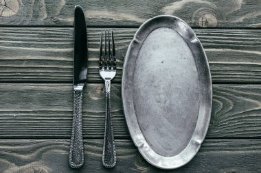 Knife and fork with silver tray on wooden table