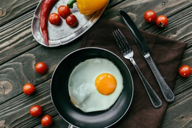 Clean eating concept with fried egg and raw vegetables on wooden table