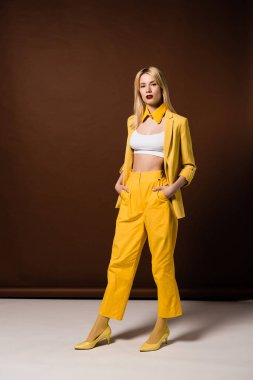 beautiful blonde woman in stylish yellow clothes standing with hands in pockets and looking at camera on brown