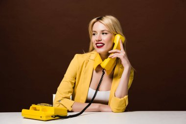 Beautiful smiling blonde girl talking by vintage telephone and looking away on brown stock vector