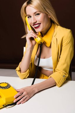 beautiful blonde girl talking by yellow vintage phone and smiling at camera on brown