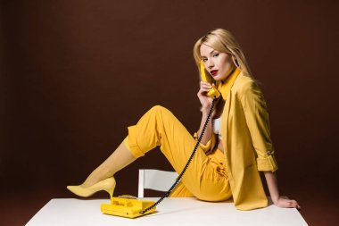 beautiful stylish blonde girl talking by yellow vintage phone and looking at camera on brown