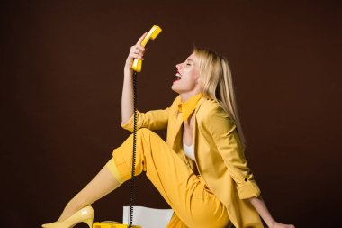 excited stylish blonde girl holding yellow handset and sitting on brown